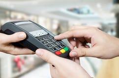 Χέρι με το ισχυρό κτύπημα πιστωτικών καρτών μέσω του τερματικού για την πώληση στο superma στοκ φωτογραφία με δικαίωμα ελεύθερης χρήσης