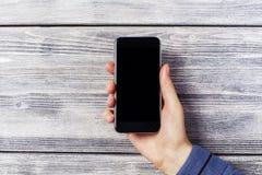 Χέρι με το μαύρο smartphone Στοκ εικόνα με δικαίωμα ελεύθερης χρήσης