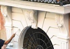Χέρι με το πινέλο που χρωματίζει μια άσπρη διακόσμηση τοίχων Στοκ Φωτογραφίες