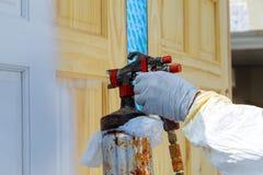 Χέρι με το πυροβόλο όπλο ψεκασμού που χρωματίζει την ξύλινη πόρτα στοκ εικόνες με δικαίωμα ελεύθερης χρήσης