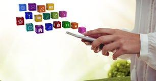 χέρι με το τηλέφωνο με τα εικονίδια εφαρμογής που εμφανίζονται από το Άσπρα και πράσινα θολωμένα φω'τα bakcground Στοκ Φωτογραφίες