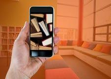 Χέρι με το τηλέφωνο που παρουσιάζει μόνιμα βιβλία ενάντια στο δωμάτιο με την πορτοκαλιά επικάλυψη Στοκ Εικόνες