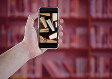 Χέρι με το τηλέφωνο που παρουσιάζει μόνιμα βιβλία ενάντια στο μουτζουρωμένο ράφι με την κόκκινη επικάλυψη Στοκ φωτογραφία με δικαίωμα ελεύθερης χρήσης