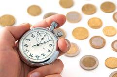 Χέρι με το χρονόμετρο με διακόπτη και τα νομίσματα Στοκ φωτογραφία με δικαίωμα ελεύθερης χρήσης