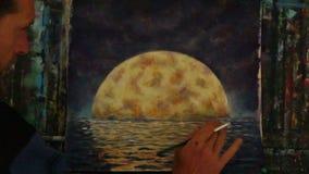 Χέρι με το χρώμα βουρτσών ένα πορτοκαλί μεγάλο φεγγάρι στο μπλε, αντανάκλαση του φεγγαριού στον ωκεανό, θάλασσα, νερό φιλμ μικρού μήκους