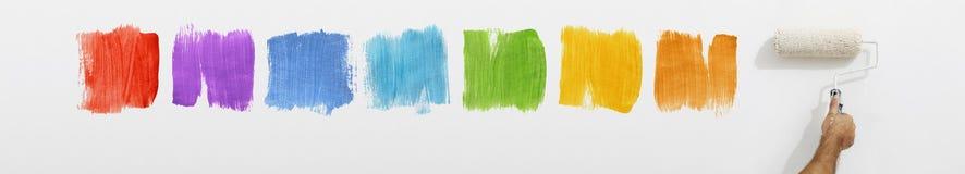Χέρι με το χρώμα κυλίνδρων στον τοίχο με τα δείγματα χρώματος Στοκ Εικόνες