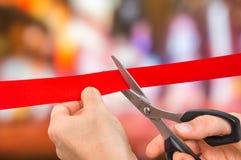 Χέρι με το ψαλίδι που κόβει την κόκκινη κορδέλλα - τελετή έναρξης Στοκ Εικόνες