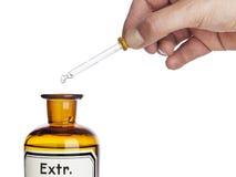 Χέρι με το eyedropper επάνω από το μπουκάλι φαρμακείων στοκ εικόνες
