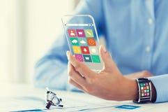 Χέρι με app τα εικονίδια στο έξυπνα τηλέφωνο και το ρολόι Στοκ Φωτογραφία
