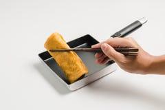Χέρι με chopsticks το τηγανισμένο ρόλος αυγό πιασιμάτων Στοκ Εικόνα