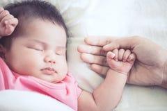 Χέρι μητέρων που κρατά το ασιατικό νεογέννητο χέρι κοριτσάκι ενώ κοιμάται στοκ φωτογραφία με δικαίωμα ελεύθερης χρήσης