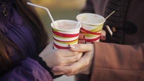 Χέρι μιας γυναίκας και ενός έφηβη που κρατούν έναν καφέ με το γάλα Κινηματογράφηση σε πρώτο πλάνο Πάρκο φθινοπώρου απόθεμα βίντεο