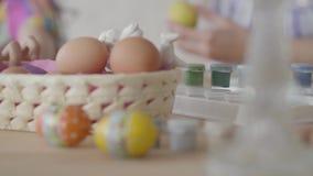 Χέρι μιας γυναίκας που λαμβάνει ένα αυγό από το καλάθι κοντά Μητέρα και κόρη που χρωματίζουν τα αυγά Πάσχας στην κουζίνα E απόθεμα βίντεο