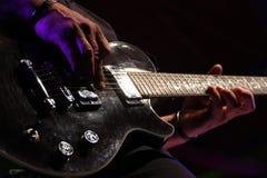 Χέρι μιας κιθάρας παιχνιδιού ατόμων Στοκ Φωτογραφία