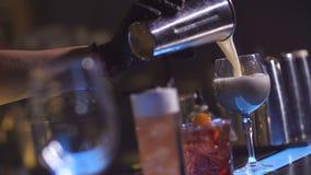 Χέρι μπάρμαν που χύνει το έτοιμο κοκτέιλ έξω από το δονητή φιλμ μικρού μήκους