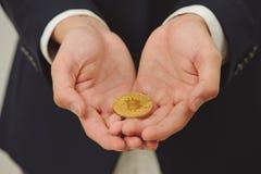 Χέρι νεαρών άνδρων που κρατά ψηλά το χρυσό bitcoin στο χέρι δύο Κλείστε επάνω το ο Στοκ φωτογραφία με δικαίωμα ελεύθερης χρήσης