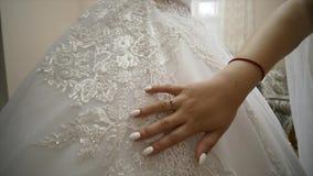 Χέρι νυφών ` s που χαϊδεύει ένα γαμήλιο φόρεμα closeup φιλμ μικρού μήκους