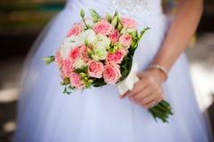 Χέρι νύφης με μια ανθοδέσμη στο υπόβαθρο του φορέματος Στοκ Εικόνα