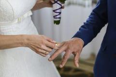 Χέρι νύφης που βάζει ένα γαμήλιο δαχτυλίδι Στοκ Εικόνες