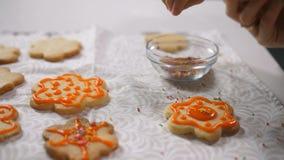 Χέρι παιδιού που διακοσμεί τα ψημένα μπισκότα με την τήξη απόθεμα βίντεο