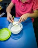Χέρι παιδιών που εκσκάπτει και που χρησιμοποιεί chopstick για να ισοπεδώσει το άσπρο powde Στοκ Φωτογραφίες