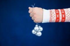 Χέρι παιδιών που κρατά τα ασημένια μπιχλιμπίδια Χριστουγέννων στοκ φωτογραφία με δικαίωμα ελεύθερης χρήσης