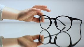 Χέρι παιδιών που παίρνει τα θεάματα, διάγνωση της όρασης παιδιών, βοήθεια οφθαλμολογίας φιλμ μικρού μήκους