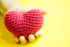 Χέρι παιδιών ` s με μια κόκκινη καρδιά στο κίτρινο υπόβαθρο στοκ φωτογραφία με δικαίωμα ελεύθερης χρήσης