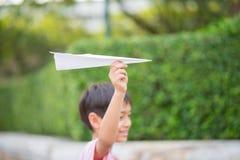 Χέρι παιδιού που παίρνει το έγγραφο αεροπλάνων παιχνιδιού το πάρκο Στοκ εικόνες με δικαίωμα ελεύθερης χρήσης