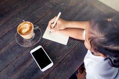 Χέρι παιδιών εκμετάλλευσης χεριών μητέρων που γράφει στο σημειωματάριο Στοκ Εικόνα
