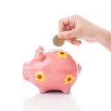 Χέρι παιδιών που βάζει ένα νόμισμα στη piggy τράπεζα Στοκ Φωτογραφία