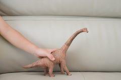 Χέρι παιδιών που πιάνει ένα παιχνίδι brachiosaurus σε έναν καναπέ Στοκ Εικόνες