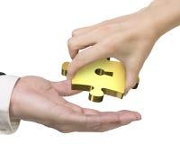 Χέρι που δίνει ένα χρυσό κομμάτι γρίφων με την κλειδαρότρυπα στοκ εικόνα με δικαίωμα ελεύθερης χρήσης