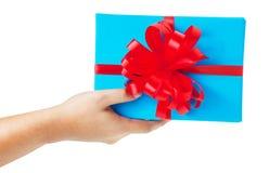 χέρι που δίνει ένα δώρο που τυλίγεται στο μπλε κιβώτιο Στοκ φωτογραφίες με δικαίωμα ελεύθερης χρήσης