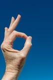 Χέρι που δίνει το καθολικό ΕΝΤΑΞΕΙ σημάδι στο υπόβαθρο ουρανού Στοκ φωτογραφίες με δικαίωμα ελεύθερης χρήσης