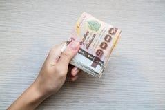 Χέρι που δίνει το σωρό χιλιάες ταϊλανδικών χρημάτων λουτρών Στοκ Εικόνες