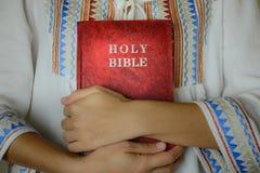 Χέρι που αγκαλιάζει την κόκκινη ιερή Βίβλο Στοκ Φωτογραφίες