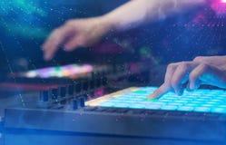Χέρι που αναμιγνύει τη μουσική στον ελεγκτή του DJ με τα χρώματα λεσχών κομμάτων γύρω Στοκ εικόνα με δικαίωμα ελεύθερης χρήσης