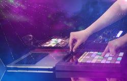 Χέρι που αναμιγνύει τη μουσική στον ελεγκτή του Midi με τα χρώματα λεσχών κομμάτων γύρω Στοκ εικόνα με δικαίωμα ελεύθερης χρήσης
