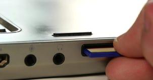 Χέρι που αφαιρεί την κάρτα μικροϋπολογιστών SD από το lap-top 4k απόθεμα βίντεο