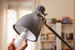 Χέρι που αλλάζει μια κανονική λάμπα φωτός για τις οδηγήσεις Στοκ Εικόνα