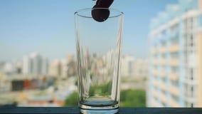 Χέρι που βάζει ένα χάπι σε ένα ποτήρι του νερού σε σε αργή κίνηση στο θολωμένο υπόβαθρο πόλεων απόθεμα βίντεο