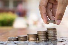 Χέρι που βάζει τα νομίσματα στη γραφική παράσταση ανάπτυξης σωρών νομισμάτων Στοκ Εικόνες