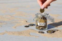 Χέρι που βάζει τα νομίσματα στο βάζο γυαλιού με την ετικέτα SAVE στοκ εικόνα