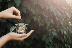 Χέρι που βάζει τα νομίσματα στο βάζο γυαλιού με την ετικέτα SAVE στοκ εικόνα με δικαίωμα ελεύθερης χρήσης