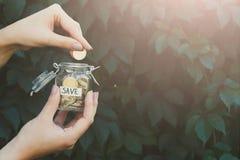 Χέρι που βάζει τα νομίσματα στο βάζο γυαλιού με την ετικέτα SAVE στοκ φωτογραφίες με δικαίωμα ελεύθερης χρήσης