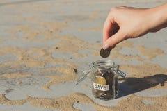 Χέρι που βάζει τα νομίσματα στο βάζο γυαλιού με την ετικέτα SAVE στοκ εικόνες