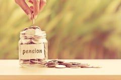 Χέρι που βάζει τα νομίσματα στο βάζο γυαλιού για το χρόνο στην αποταμίευση χρημάτων για το pe Στοκ Φωτογραφίες