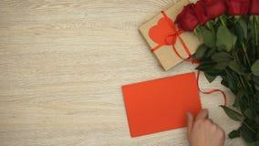 Χέρι που βάζει την κόκκινη ευχετήρια κάρτα κοντά στο κιβώτιο δώρων και τη δέσμη των τριαντάφυλλων, ημέρα βαλεντίνων απόθεμα βίντεο