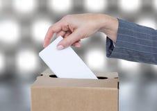 Χέρι που βάζει την ψηφοφορία στο κάλπη με το λαμπιρίζοντας ελαφρύ υπόβαθρο bokeh Στοκ Εικόνες